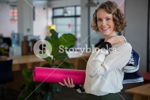 Female graphic designer with sneakers and yoga mat