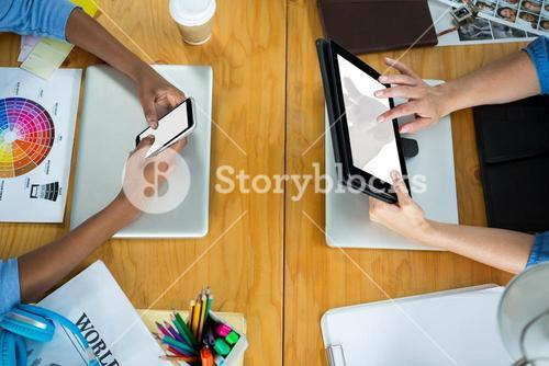 Female graphic designers using mobile phone and digital tablet on desk