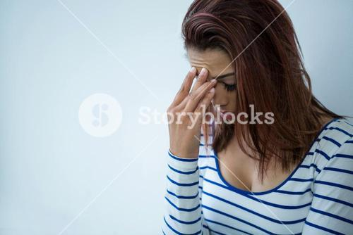Worried woman with head in hands