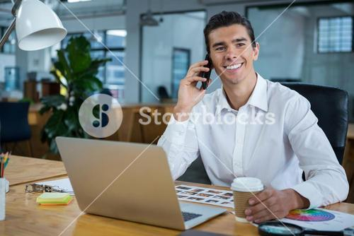 Man talking on mobile phone at desk