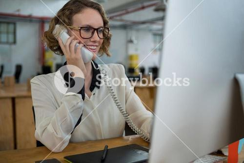 Woman talking on landline phone at desk