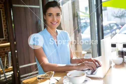 Female executive working on laptop in café