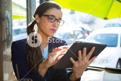 Business executive using digital tablet in café