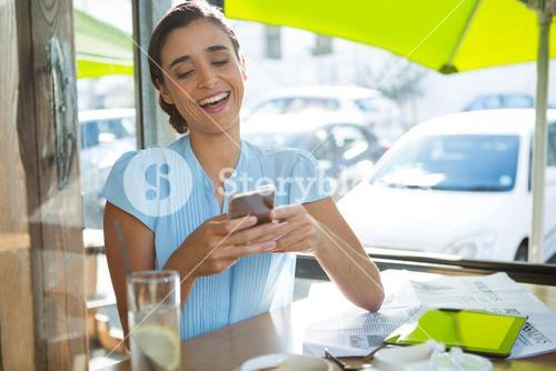 Female executive using mobile phone in café