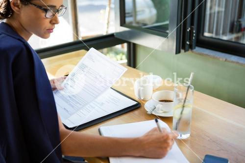 Female executive writing in diary at café