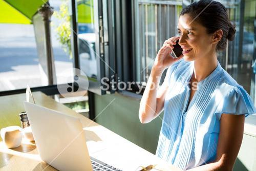 Female executive talking on mobile phone in café