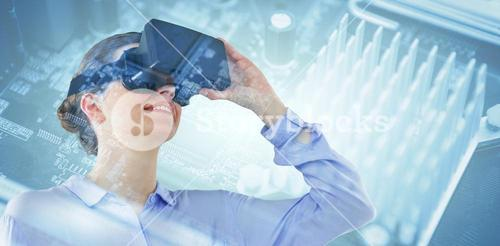 Composite image of low angle view of businesswoman using virtual reality headset