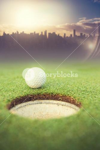 Composite image of golf ball at the edge of the hole