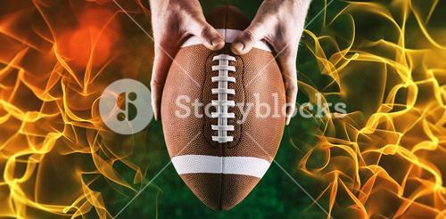 Composite image of american football player holding up football