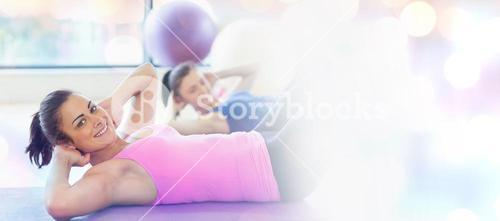 Composite image of two fit young women doing pilate exercises