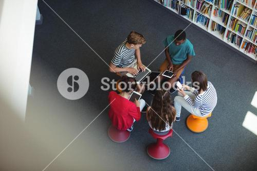 Students using laptop, mobile phone, digital tablet in library