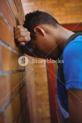 Sad schoolboy leaning on brick wall