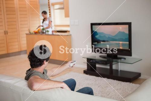 Man watching tv while his girlfriend is in the kitchen