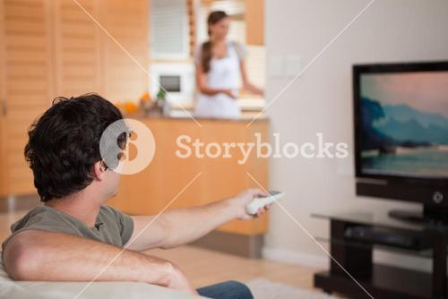 Man watching television while his girlfriend is preparing dinner