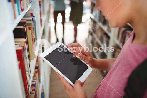 Schoolboy using digital tablet in library