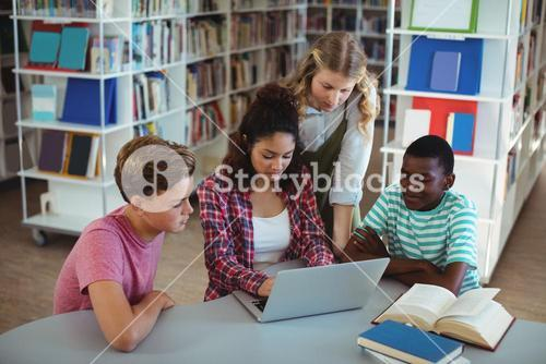 Attentive classmates using laptop in library