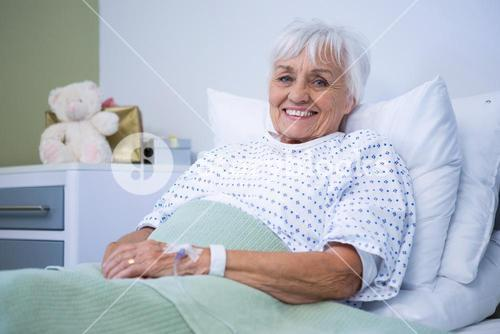 Portrait of smiling senior patient on bed