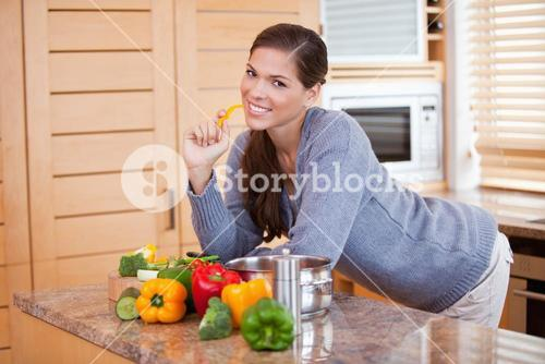 Smiling woman with healthy vegetables in the kitchen