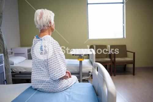 Rear-view of thoughtful senior patient sitting on bed