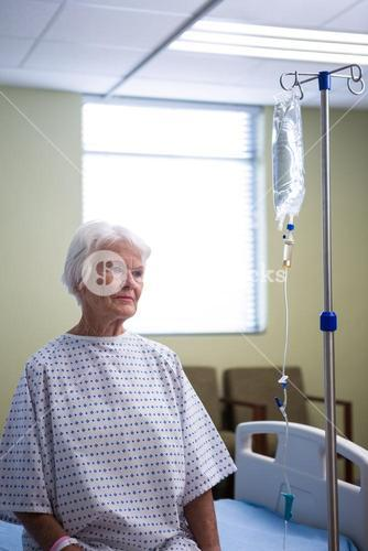 Thoughtful senior patient standing at hospital