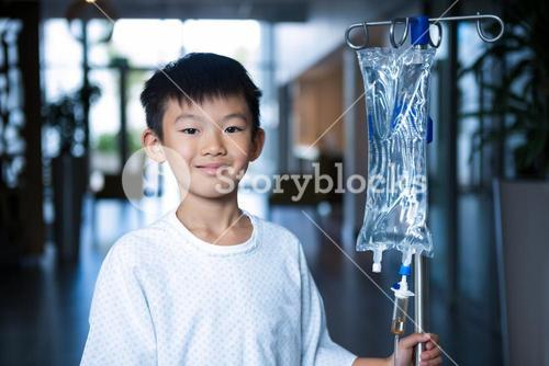 Smiling boy patient holding intravenous iv drip stand in corridor