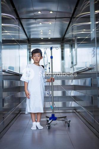Smiling boy patient holding intravenous iv drip stand in lift