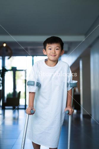 Boy patient walking with crutches in corridor