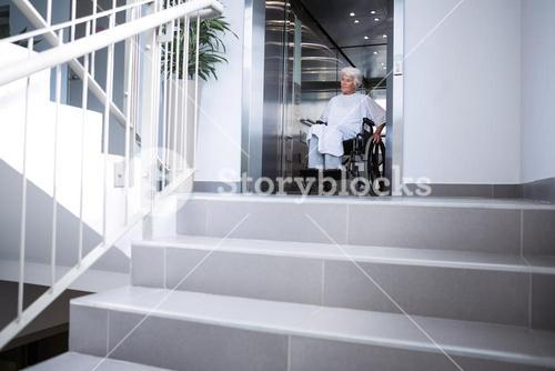 Disabled senior patient on wheelchair in lift