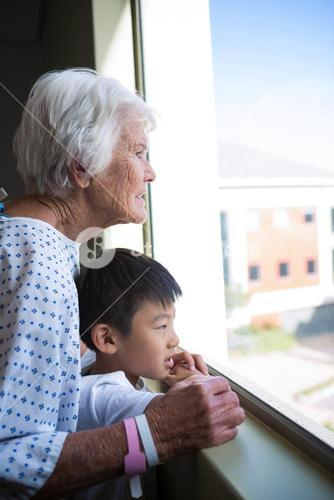 Senior patient and boy looking out from the window