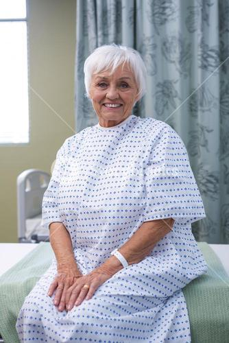 Smiling senior patient sitting on bed in hospital