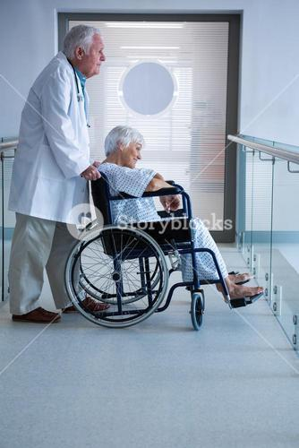Doctor and senior patient on wheelchair in the passageway