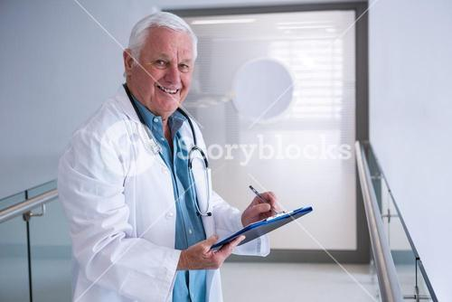 Doctor writing on clipboard in the passageway at hospital