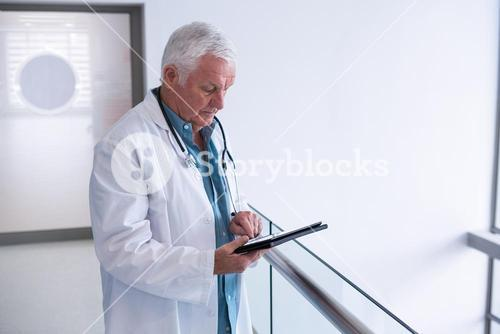 Doctor using a digital tablet in the passageway