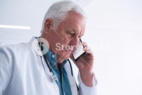 Doctor talking on his mobile phone in the passageway
