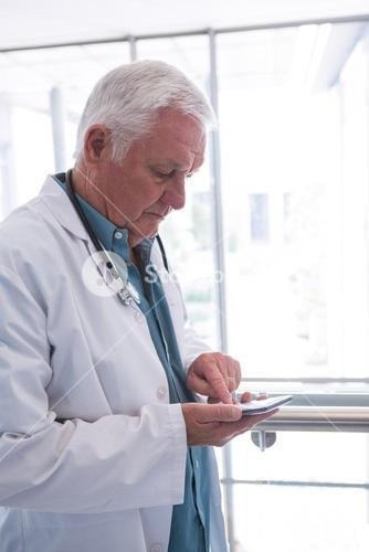 Doctor holding smartphone in the passageway