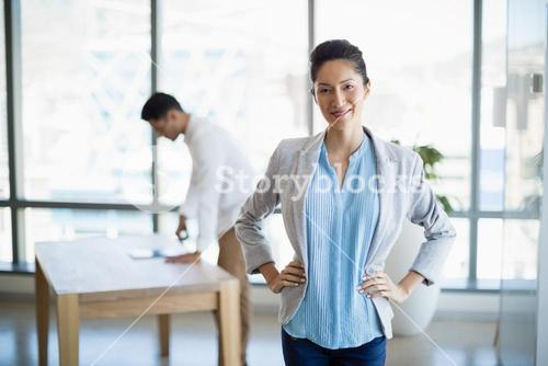 Portrait of smiling business executive standing with hands on hip
