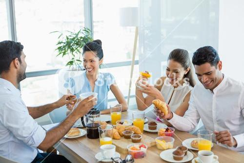 Business colleagues interacting with each other while having breakfast
