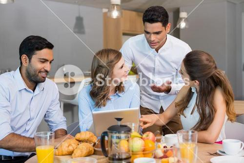 Business colleagues discussing over digital tablet while having breakfast