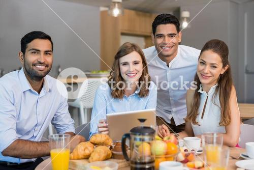 Business colleagues discussing over digital tablet while having breakfast in office cafeteria