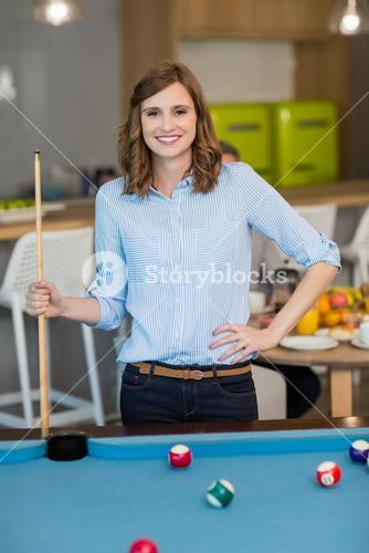 Portrait of smiling business executive playing pool