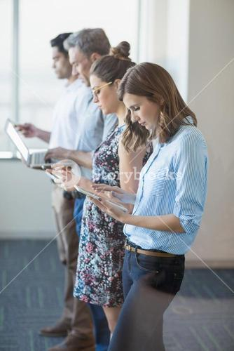 Business colleagues standing in a row using mobile phone, digital tablet and laptop