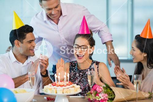 Smiling colleagues celebrating birthday of woman
