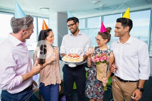Smiling business colleagues celebrating birthday