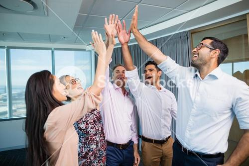 Business colleagues giving high five during meeting in office