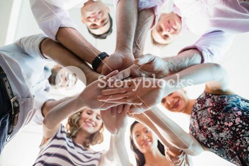 Portrait of smiling business colleagues with their hands stacked