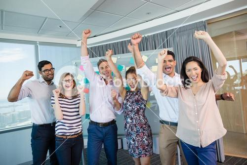 Portrait of smiling business colleagues cheering with fists up