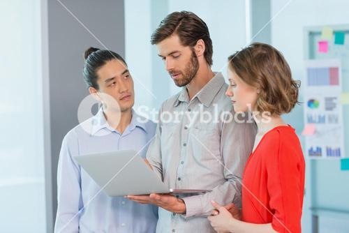 Business executives discussing over laptop