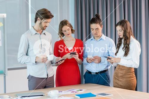Business executives using mobile phones in conference room