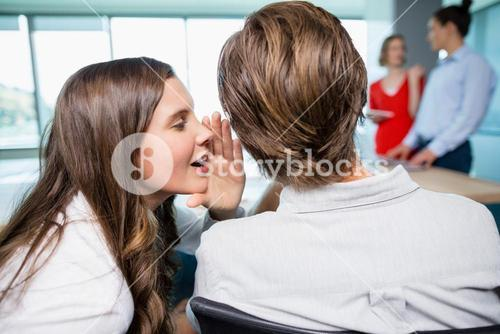 Business executive whispering in her colleagues ear