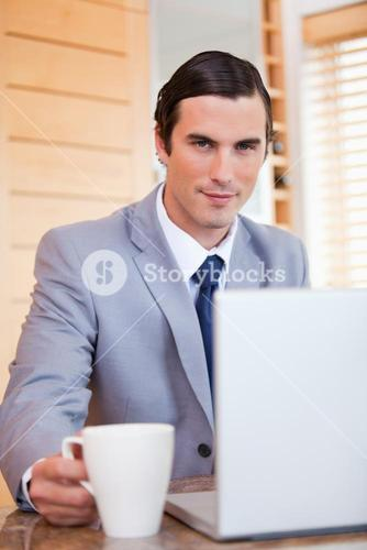 Businessman with laptop and tea